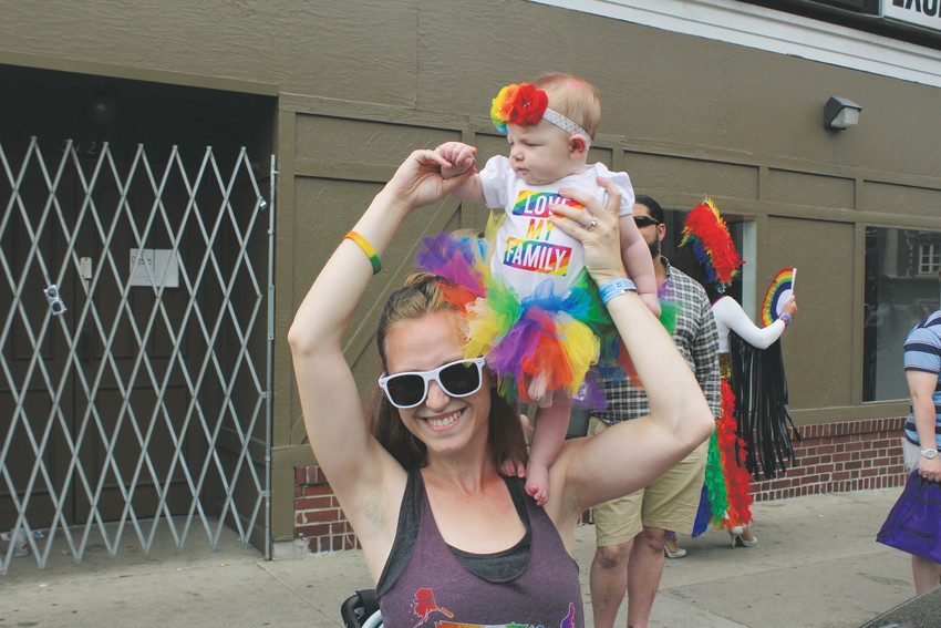Lexi Allen holds Maia Allen while watching the Pride Parade from Colfax Avenue on June 17.