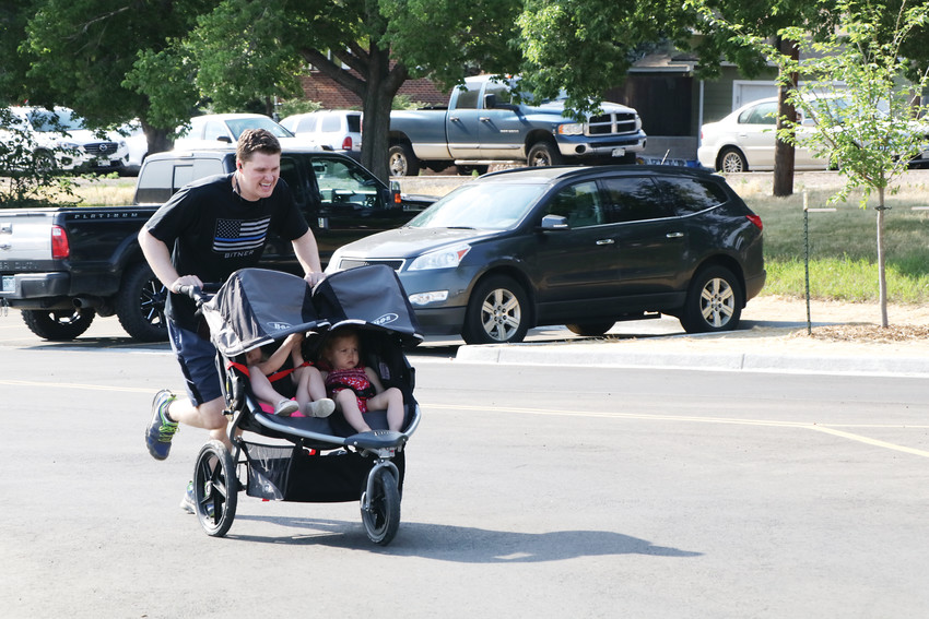 Garrick Storgaard pushes his double stroller across the finish line as he is one of the runners and walkers who took part in the June 15 Jeremy Bitner Memorial Run and Walk. The event is held in memory of Detective Jeremy Bitner who was killed in the line of duty and raises money for the Fallen Officers Fund.