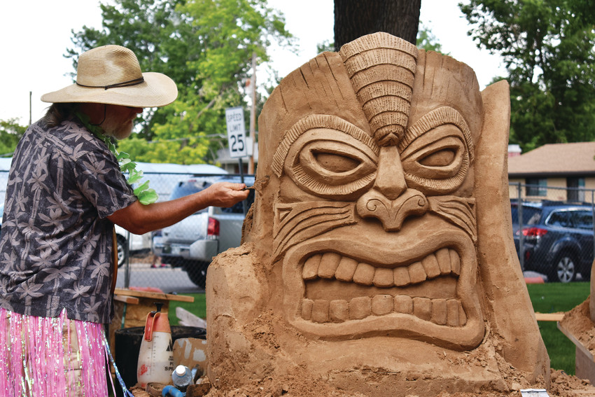 Sand in the City coach Bert Adams carves the coach's sculpture.