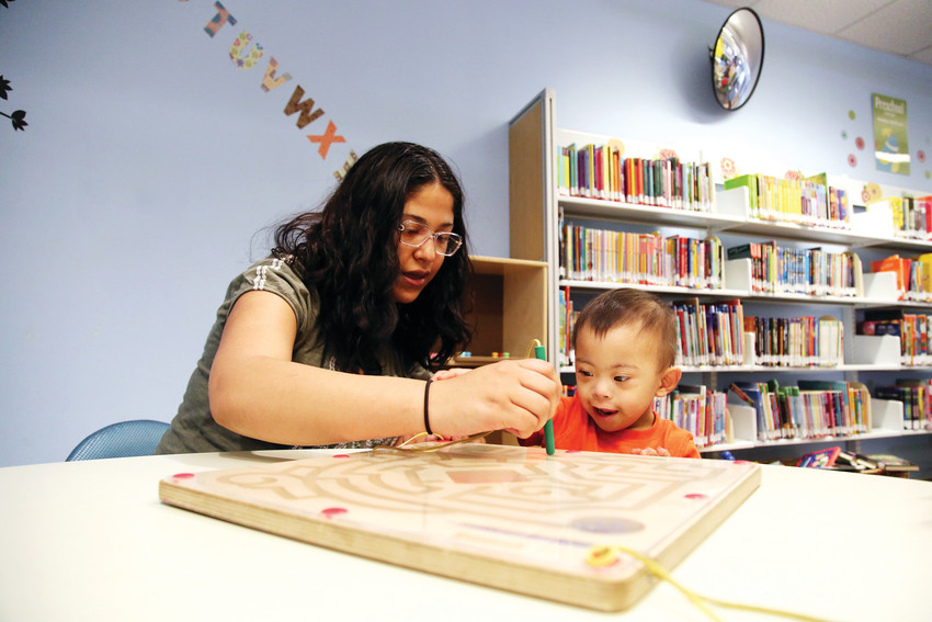 Leslie Belmontes playes with her son, Aaron, at the Bear Valley Branch Library in Denver.