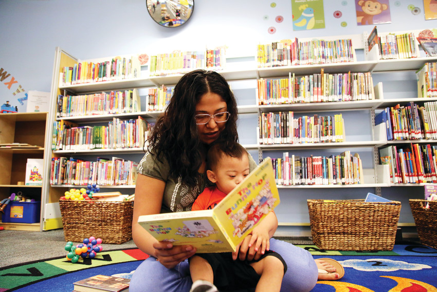 Leslie Belmontes, 19, reads with her 2-year-old son, Aaron, at the Bear Valley Branch Library in Denver. Belmontes dropped out of high school after becoming a mom.