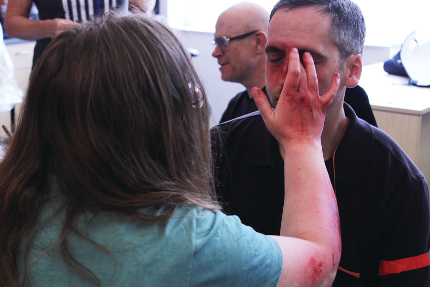 An actor has broken nose make-up applied to his face for the active shooter drill.