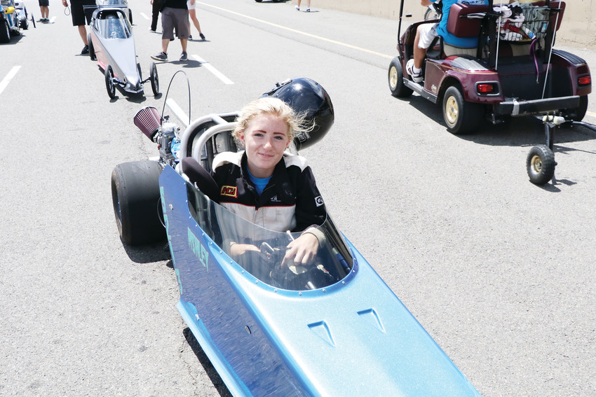 Ashley Boswick lowers herself into the cockpit of the car as she waits her turn on the starting line at the June 23 session of the Division 5 Junior Dragster Championship races at Bandimere Speedway. The Centennial resident was among 122 drivers who competed in the races.