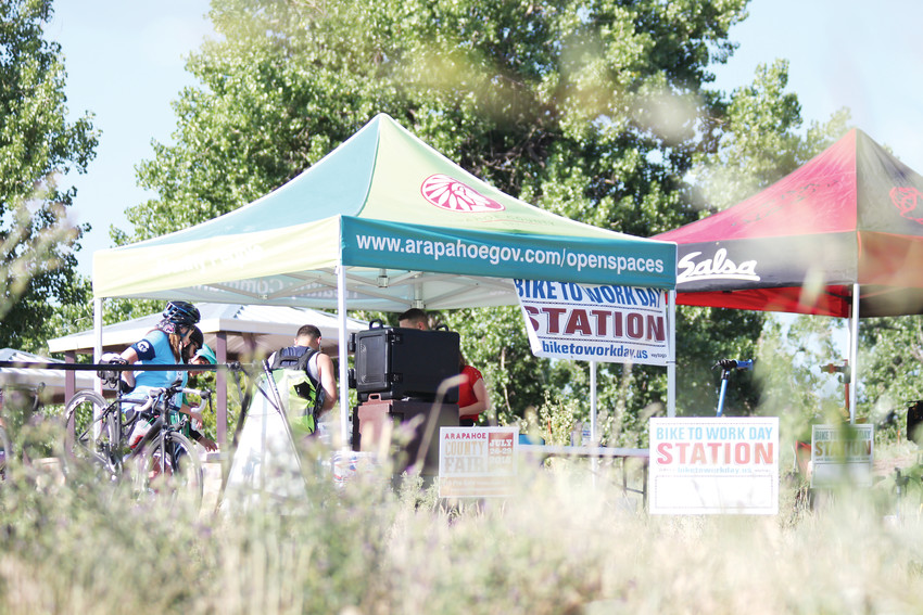 At right, riders take a break under the Arapahoe County Open Spaces tent at Reynolds Landing Park.