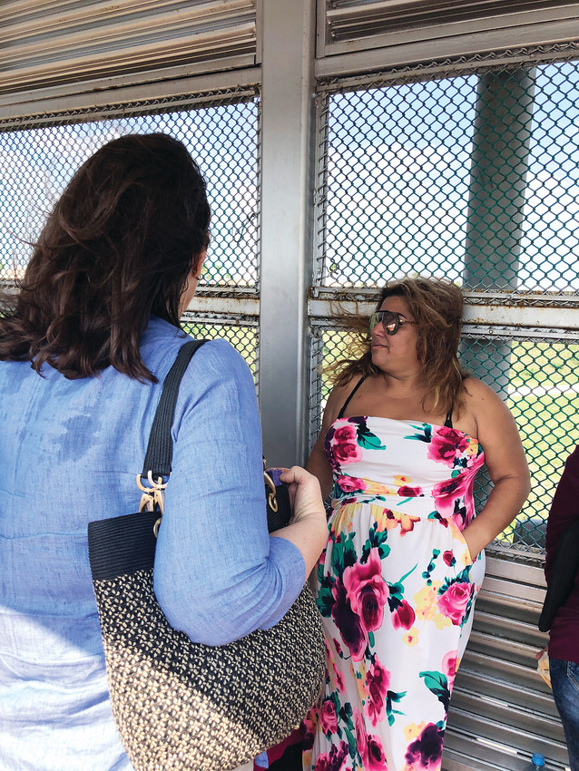 "Rep. Diana DeGette, left, speaks with migrants hoping to cross the border at the Gateway International Bridge in Brownsville, Texas, on June 23. She also toured a ""tender age"" facility in Brownsville."