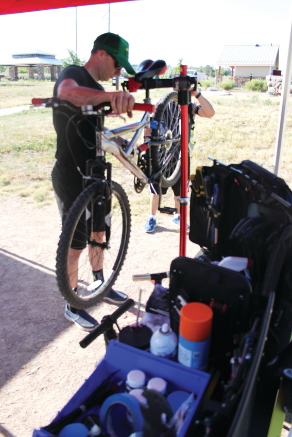 "Pedal Littleton service manager Justin Sheldon does some field hospital work on a commuter's bike. ""We can fix a good chunk of the problems a rider can run into with just a toolbox,"" Sheldon said."