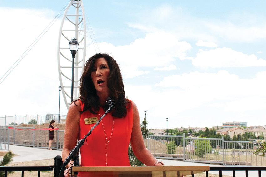 Lone Tree Mayor Jackie Millet speaks in front of a crowd of about 75 at Snooze restaurant during the ribbon cutting ceremony for the Lone Tree Leaf Pedestrian Bridge June 28.