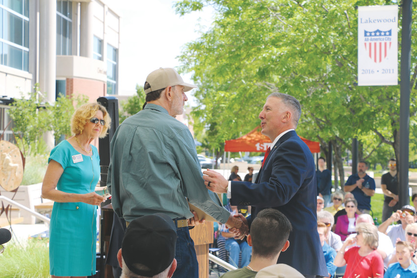 Jefferson County Manager and retired Marine Don Davis, gives a member of the Jeffco Platoon a Vietnam Veteran Lapel Pin at the Lakewood Civic Ceremony reunion event on June 30 as Kathryn Wirkus, constituent services representative for U.S. Rep. Ed Perlmutter, looks on.