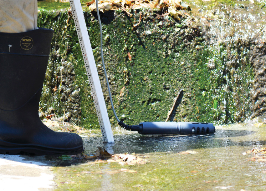 Duke Douglas drops a sensor into a puddle in a canal. The sensor tests water conductivity as well as temperature, salinity and pH balance, looking for potential pollution.