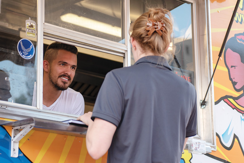 Jorge Dominguez, owner of the Arepa's House food truck, helps a customer ordering lunch at Civic Center EATS in June at Civic Center Park in Denver. Dominguez and his truck have been at the event for three years and it is one of the more popular food destinations there.