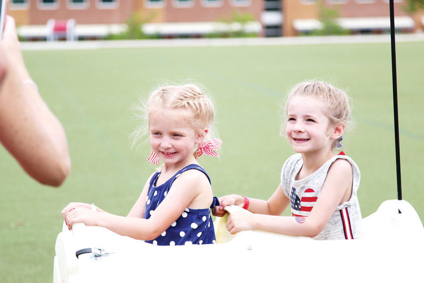 Paige Spicer, 5, and Amelia Biondolillo, 5, smile as they climb in their seats for a train ride at Fourth of July celebration in The Meadows.
