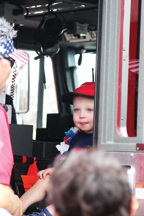 Boden Bishop, 2, peeks out from a Castle Rock fire truck on July 4. Bishop and his family traveled from Parker to take part in The Meadows' celebration.