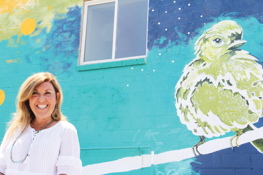 Catherine Pistone, painter of the mural on the north wall of HOPE food pantry and HOPE's Attic thrift store, stands in front of her work July 7 at the celebration ceremony for the mural. Pistone, a Boulder-based artist, produced her first-ever mural for that building.