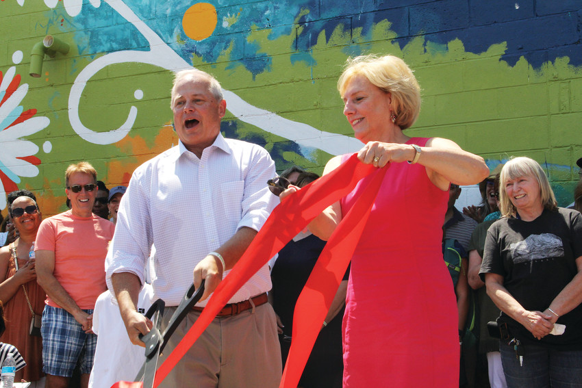 Bart Sayyah, front left, and Arapahoe County Commissioner Nancy Sharpe cut the ribbon at the celebration ceremony July 7 for the mural at HOPE food pantry and HOPE'S Attic thrift store. Sayyah is the executive director of HOPE, located at 3940 S. Broadway in Englewood.
