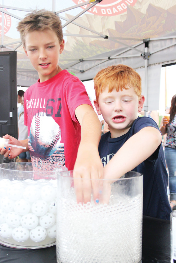 Jonah Denny-Mayo, left, and Ryder Pilz stick their hand in a tub of gel beads intended to demonstrate the nitrogen-bubble infused nature of many Breckenridge brews, though presumably neither of the kids got to try any of the relevant beers.