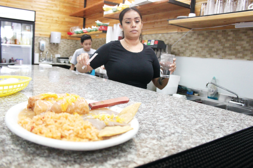 Maria Navarro serves up a plate of crispy chile rellenos at El Lucero, her family's restaurant. The popular eatery reopened at Woodlawn Shopping Center recently after a years-long hiatus.