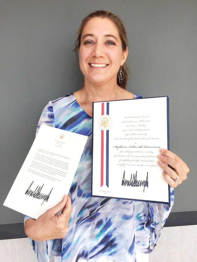 Stephanie Kawamura, a Douglas County teacher and recipient of the Presidential Award for Excellence in Mathematics and Science Teaching (PAEMST), holds up two honors signed by President Donald Trump. Kawamura was one of two teachers in Colorado to receive the honor.