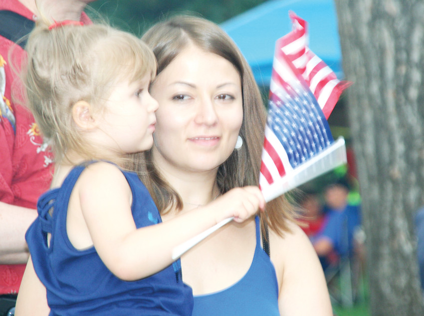 Julia Nesvat of Parker holds her daughter Polina, 3, as she waves a mini American flag at this year's Fourth of July celebration at Lions Park in Golden.