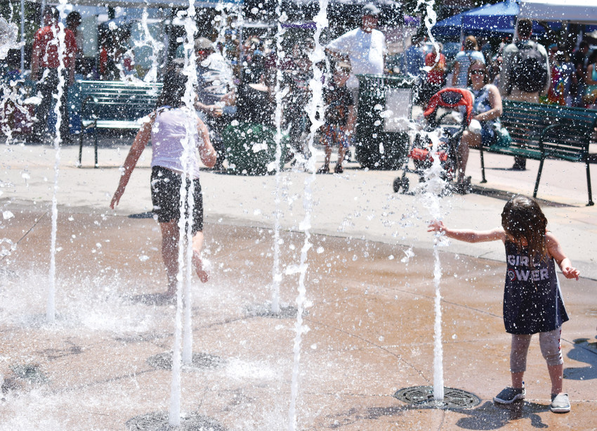 Above, Everly Sampson, 2, stays cool in the fountains in Olde Town Square.