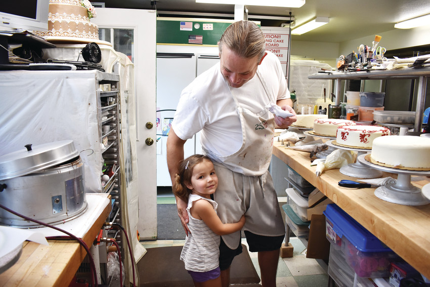 Noelle Meyer, 4, hugs Zach Meyer. A huge emphasis is placed on family at the bakery, and all three generations of the Meyer family can be seen helping out at the bakery.