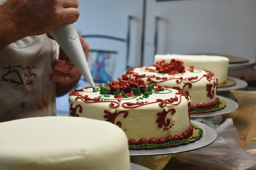 Zach Meyer carefully places the finishing touches on a cake to display at the storefront.