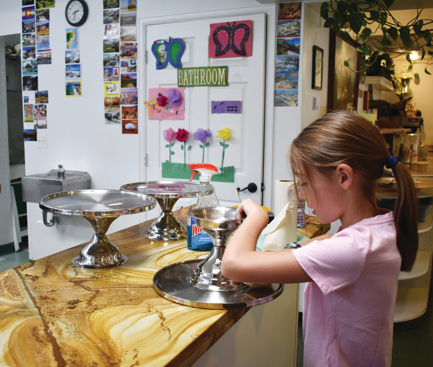 Laina Meyer, 9, polishes cake stands in her family's bakery.