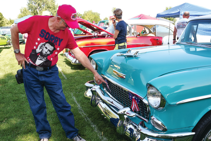 Bob Bryant of Erie, explains differing grille designs on a 1955 Chevrolet Bel Air, at Northglenn's Fourth of July Car Show, at E.B. Rains, Jr. Memorial Park, July 4. Vehicles such as his, can easily fetch $48,000 to $55,000 at classic car auctions.