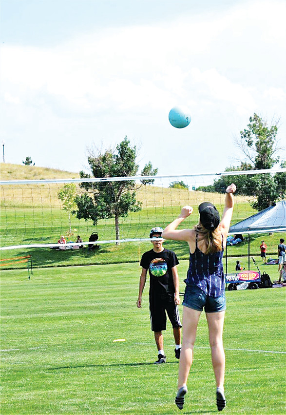 Rachel Hays of Westminster jumps up to return the volleyball to David Smith across the net July 4 in Westminster's City Park.