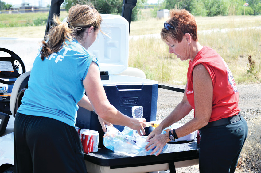 Westminster Parks and Recreation staffers Stephanie Musella and Kimberly Chrisman fill up a cooler with bottles of water for performers at Westminster's July 4 celebration at City Park.