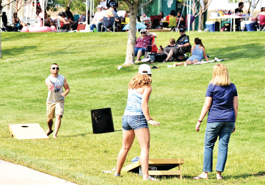 Tyler Linzy makes a shot at a cornhole target he and friends set up at Westminster's July 4th Celebration at City Park. Beginning at 4 p.m., the park began filling up with people ready to enjoy a later afternoon in the park and an evening of fireworks.