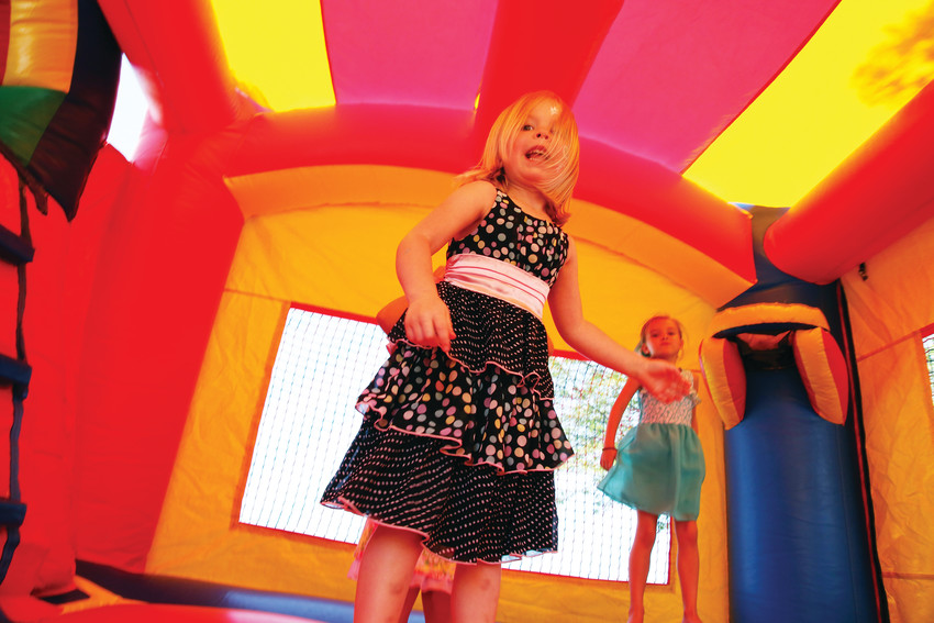 Isabella Meredith, 4, jumps in the bounce house July 10, at the summer bash at the Arvada Marketplace Connection.