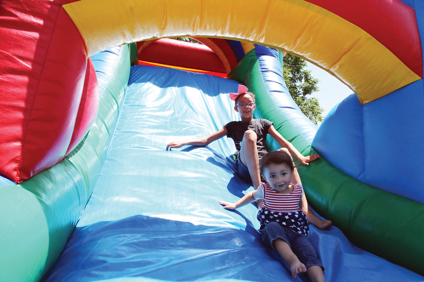 Sisters Zoe and Katen Sangater enjoy the bounce house at the Arvada Marketplace Connection summer bash.