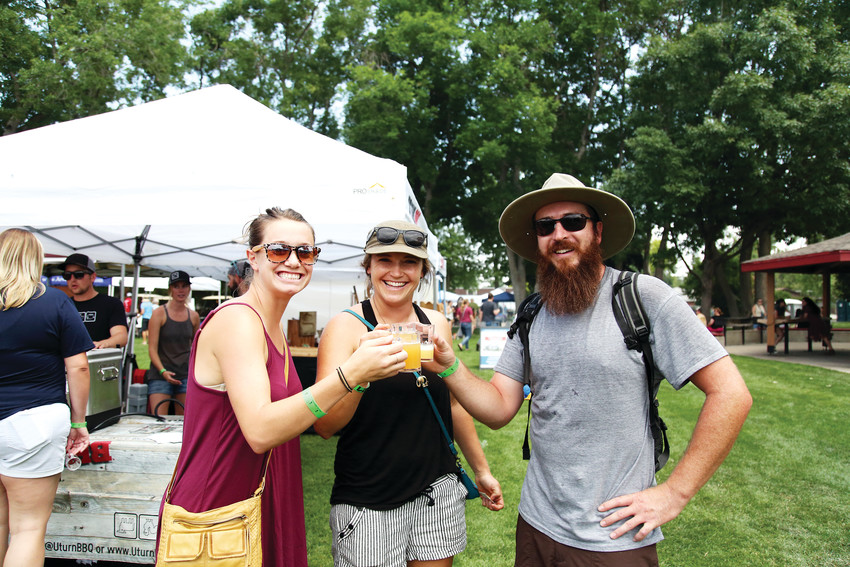 Festival attendees Nicole Kluk, Maddie Stephens and Alex Clifford cheers before tasting their beer sample.