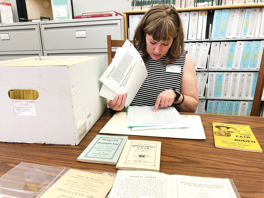 Alyssa Carver, an archivist with Douglas County Libraries, examines historic fair programs and articles in the library's archive on the Douglas County Fair & Rodeo.