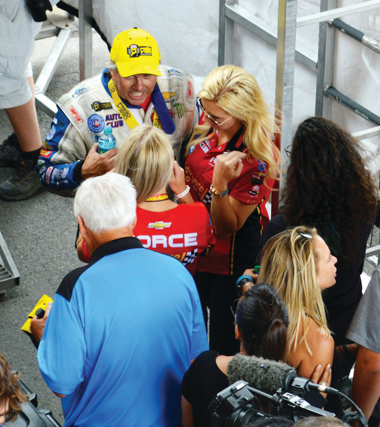 Funny car winner John Force talks with his daughter Courtney, right, and injured Marine Kirstie Ennis following his victory in the funny car finals July 22 at the Dodge Mile-High Nationals at Bandimere Speedway.