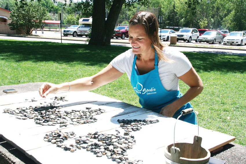 Charlotte Bassin of Golden creates one of her world maps in Lions Park during ARTSWEEK GOLDEN,  at various in-and-outdoor venues.