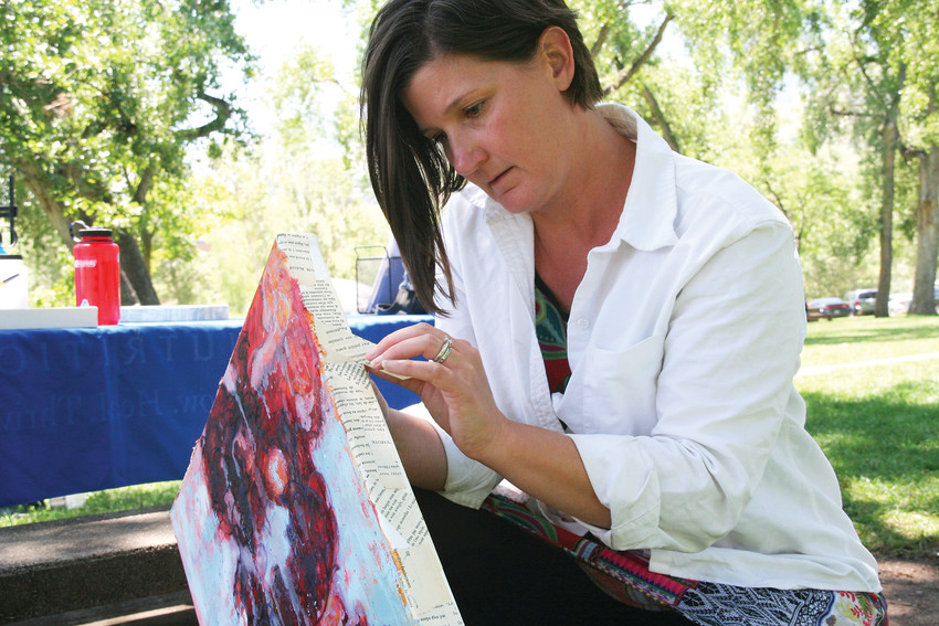 Nikki Nienhuis of Golden glues on antique French poetry on her mixed media abstract oil piece in Lions Park during ARTSWEEK GOLDEN, an event put on by Foothills Art Center that took place July 16-22 at various in-and-outdoor venues.