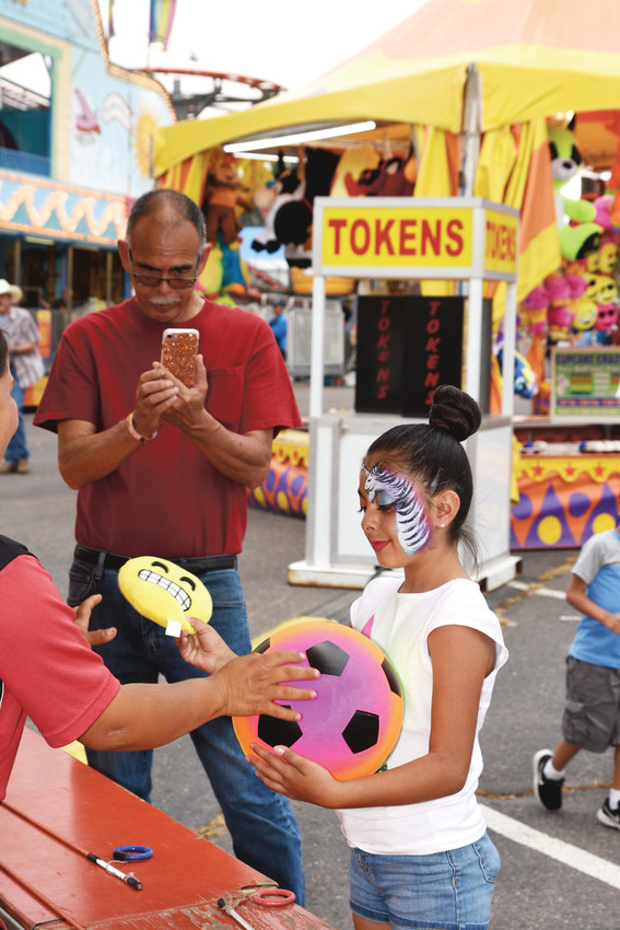 Nariah Aranda, 8, of Northglenn, exchanges gift prizes she won during a carnival game at the Adams County Fair, Friday, August 4, as her grandfather Daniel records the moment via cellphone camera.
