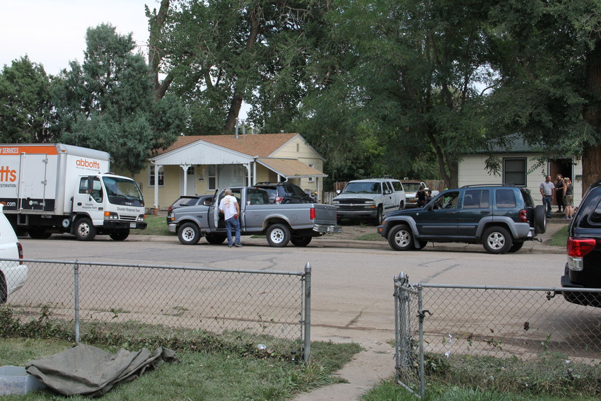At left, a flood-response truck sits on the 4600 block of South Acoma Street July 25 as neighbors and community members talk less than a day after rushing flood waters left several households damaged. Not pictured, Angelo Maldonado, 41, and his landlord, Beth Minnick, stood on the porch and discussed the damage at 4661. S. Acoma St.