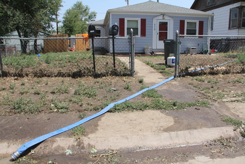 A hose leads from the home at 4668 S. Acoma St. July 25 amid water-pumping efforts after the July 24 flooding. The 4600 block of South Acoma Street and the area around it saw rushing waters that left several households displaced.