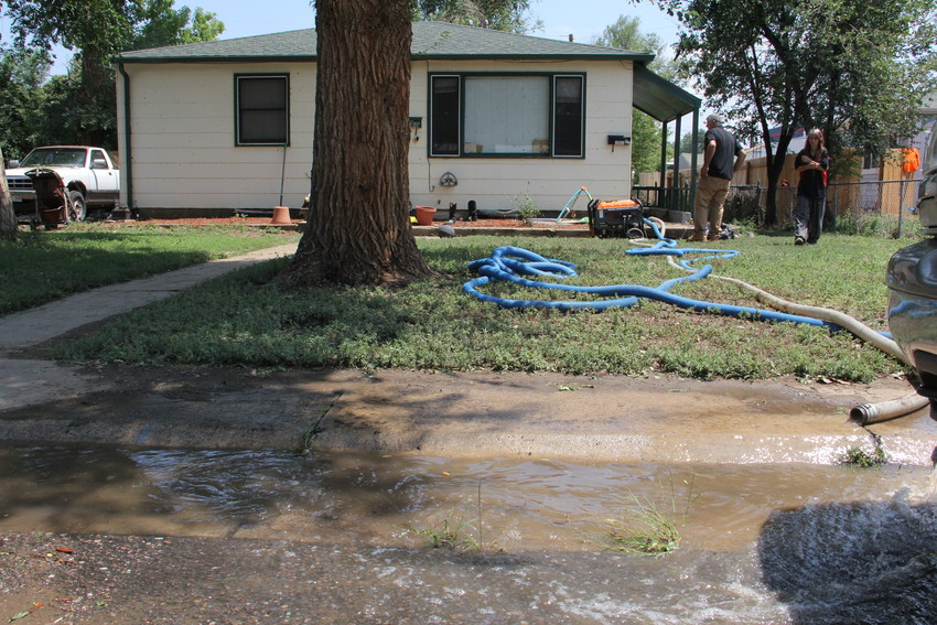 On right, Jolee Dreher, 40, looks onward July 25 as workers pump water out of her basement at 4660 S. Acoma St. The 4600 block of South Acoma Street and the area around it saw rushing flood waters July 24 that left several households displaced.