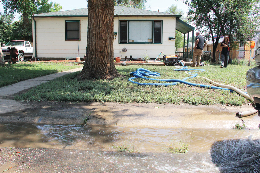 On right, Jolee Dreher, 40, looks on July 25 as workers pump water out of her basement at 4660 S. Acoma St. The 4600 block of South Acoma Street and the area around it saw rushing flood waters July 24 that left several households displaced.
