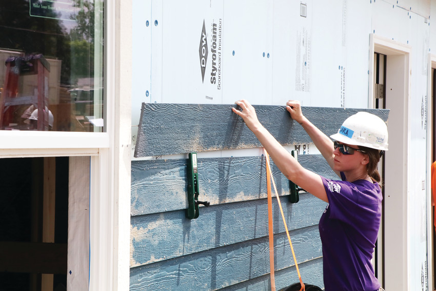 Littleton resident Cara Hyndman helps put up siding on the Sheridan Square Habitat for Humanity project. Hyndman and about 50 other Wells Fargo employees took part in the Women Work Week. They spent July 25 working on a couple of the 63 homes that will make up the project.