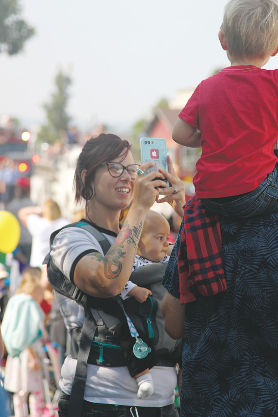 Zoe Mcavenia takes a photo of her son, Killian, 2, and husband, Hayden, while wearing 6-month-old Arlo at the parade in Castle Rock on July 28.