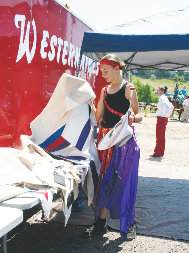 McKenzie Dawson, 14, of Thornton grabs her costumes prior to the Western Heritage Show, an annual event that celebrates the National Day of the Cowboy on July 25 outside of Fort Westernaire. Dawson performed with batons and rode with the Royal Rangers.