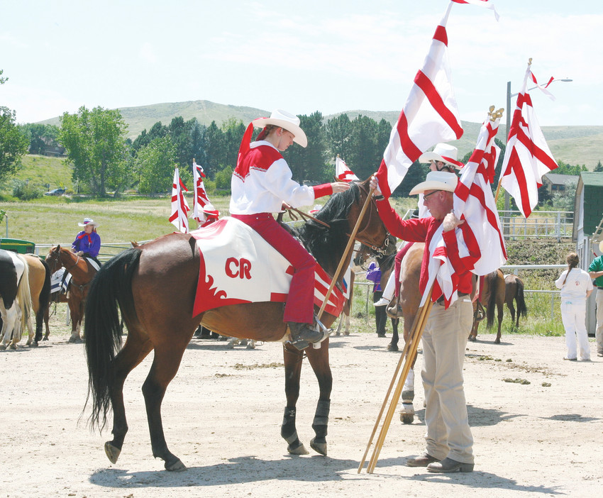 Glen VanHorn, one of the 300 or 400 adults who volunteer with the Westernaires, passes out flags on July 25 as the youth get ready for their performance at the Western Heritage Show, a free event where community members are invited to celebrate National Day of the Cowboy.