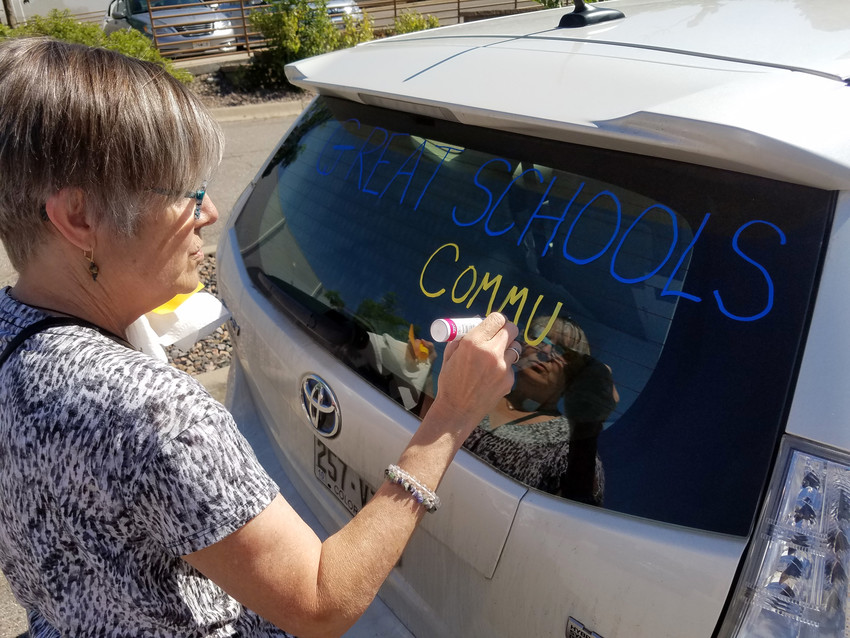 Volunteer Renee Howell paints a car that would later transport boxes of Initiative 93 signatures June 11 to the Secretary of State's office.