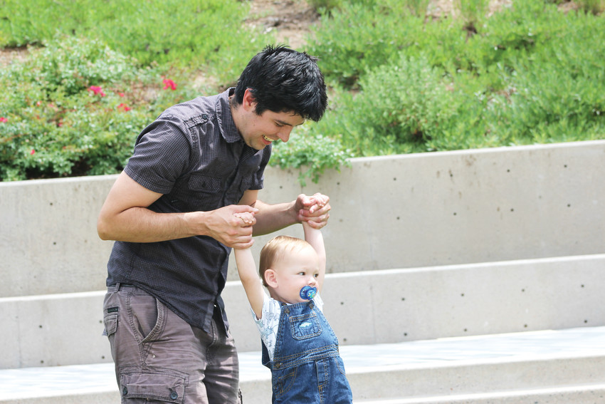 Carlos Hink and his son, Elliott, play at lunch time on the lawn of the Charles Schwab amphitheater in Lone Tree.