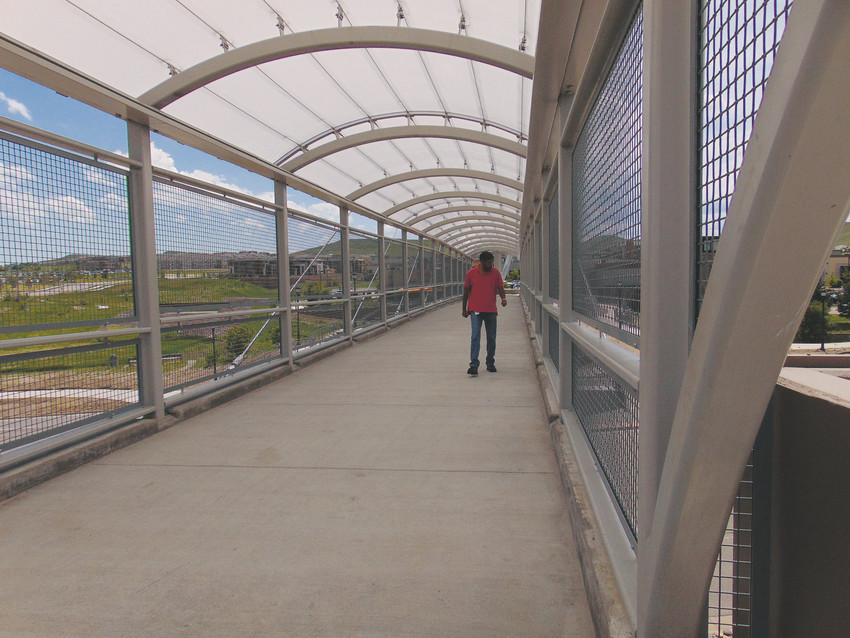 "Charles Schwab employee Zubair Ali, 55, walks across Lone Tree's Leaf Pedestrian Bridge for the first time Tuesday, May 22. ""It looks good. That Jasmine Chinese and Asian Cafe is my favorite one,"" he said, expressing happiness at being able to easily access his favorite restaurants on the other side of Lincoln Avenue."