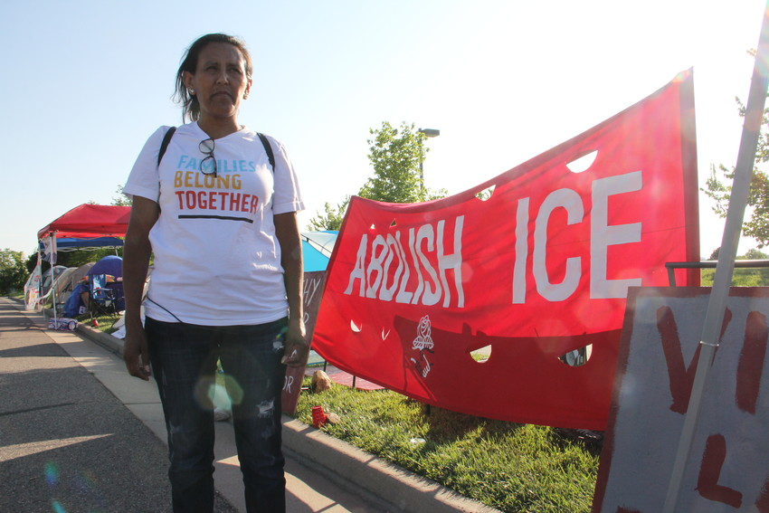 Jeanette Vizguerra, 46, stands in front of protest signs July 31 at the U.S. Immigration and Customs Enforcement (ICE) Denver Field Office at 12445 E. Caley Ave. in Centennial. Protesters, organized by Vizguerra, set up an encampment and planned to stay for a week.